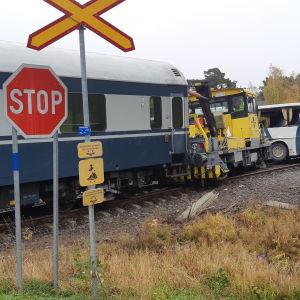 Koululaisia kuljettanut linja-auto johon on törmännyt ratakuorma-auto. Etualalalla stop-merkki