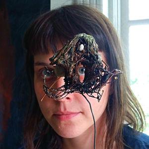 Sonja Elenius tittar genom ett hål i ett konstverk.
