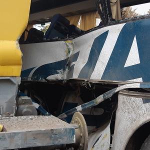 Koululaisia kuljettanut linja-auto johon on törmännyt ratakuorma-auto. lähikuva pellistä.