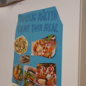 """Plansch på väggen med """"smaklig måltid""""."""