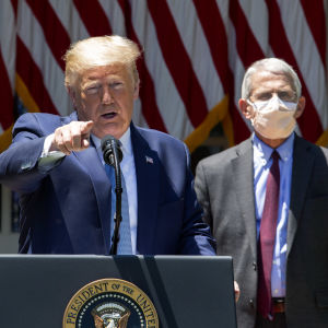 Donald Trump står vid ett talarpodium och håller presskonferens. I bakgrunden syns smittskyddsexperten Anthony Fauci som bär ansiktsskydd. Trump är utan.
