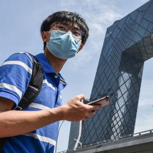 Nuori mies kännykkä kädessä. Taustalla näkyy Kiinan valtion tv:n CCTV:n rakennus.