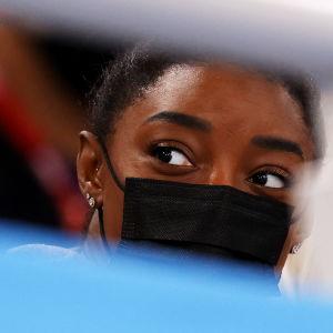 Närbild på Simone Biles iklädd munskydd som sitter på läktaren.