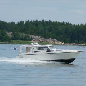 En motorbåt kör i en farled. I bakgrunden skymtar land.