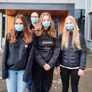 Tre skolelever står framför ingången till Nickby hjärta. Bakom dem syns en äldre man, skolans rektor. Alla har munskydd på sig.