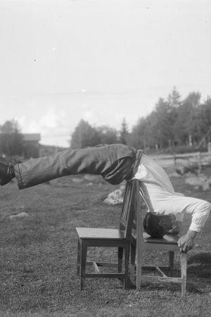 """En man leker leken """"bryta rygg"""", där han ställer sig på huvudet på en stol och lutar kroppen bakåt över en annan stol. Bilden är tagen 1931 i Närpes, Kalaks."""