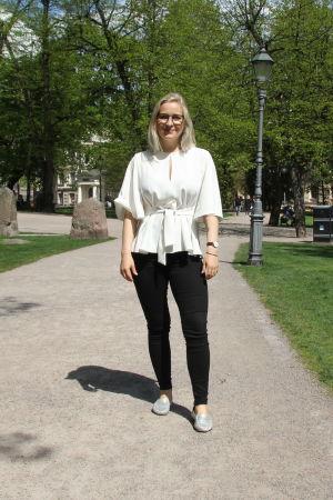 Anita Westerholm står i en park och tittar in i kameran
