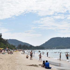 En sandstrand med parasoller och människor.