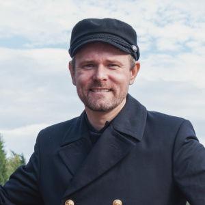 Man i kaptensuniform står i fören på en ångbåt och ler mot kameran. På hans vänstra sida står en livboj med texten S/S KOUTA.