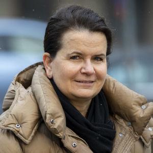 HUS biträdande överläkare Eeva Ruotsalainen står ute i en beige dunjacka. Bakom henne syns bilar parkerade.