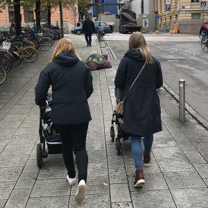 Två kvinnor promenerar med varsin barnvagn i stadsmiljö.