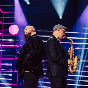 Kasmir tuijottaa eteerisesti ja keskittyy, saksofonisti Pope Puolitaival soittaa, seisovat selät vastakkain Elämäni Biisin lavalla.