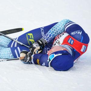 Iivo Niskanen ligger på snön.
