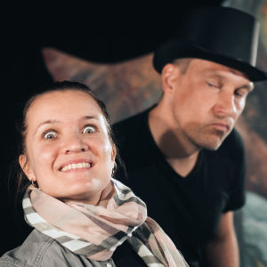 En kvinna och en man står på en teaterscen och ser in i kameran. Mannen har en hög hatt på huvudet.