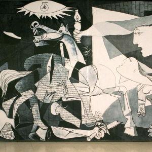 Mies tikapuilla huoltaa(?) Picasson Guernica-maalausta.