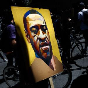Ett plakat med en tecknad bild på George Floyd. Runt plakatet ses protesterande människor.