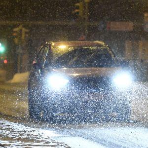 En bil med starka framlyktor kommer körande längs en snöig Nordenskiöldsgata i Helsingfors.