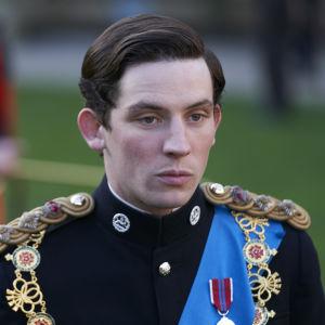 En ung man i paraduniform ser uttryckslöst fram förbi kameran.