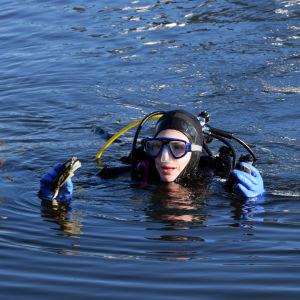 En dykare i vattnet håller något i händerna.