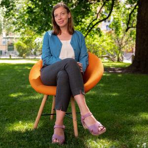 Li Andersson istuu oranssilla tuolilla puistossa.