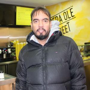 Företagaren Edgar Rodriguez driver en snabbmatskedja i Madrid. Han är en man i tidig medelålder som är ledigt klädd i en munkjacka.