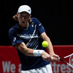 Emil Ruusuvuori slår en tennisboll gapandes.