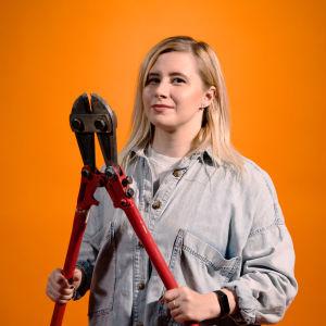 Ammattihakkeri Laura kankaala pitelee käsissään isoja pihtejä.