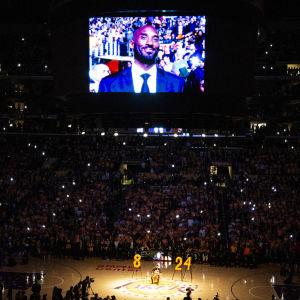 Kobe Bryant visas på sstorbildsskärmen i en mörk arena.
