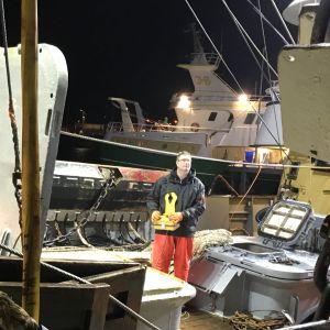 Fiskaren Cor Vonk övervakar avlastandet av fångsten ombord på däck. I handen har han en apparat för fjärrstyrningen av en vinsch.