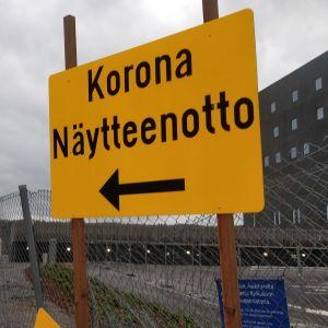 Gul skylt med text som guidar till coronatestplats.