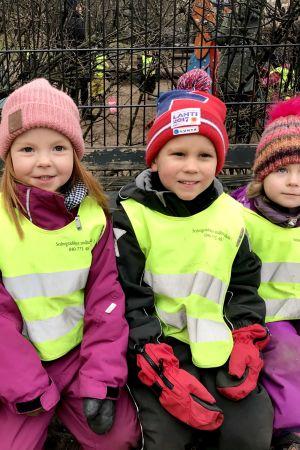 Fyra dagisbarn med gula reflexvästar på ute på parkbänk.