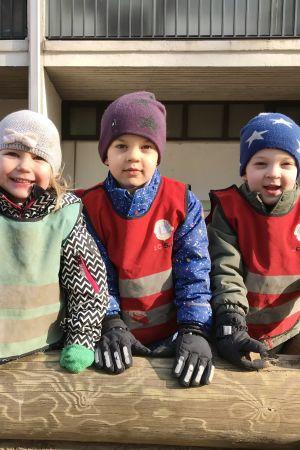 Fyra barn ute i mössor och varma kläder, Solen skiner.