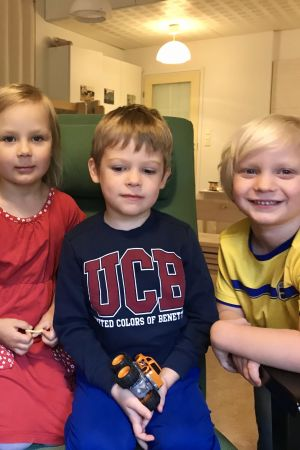 Fyra dagisbarn i en länstol.
