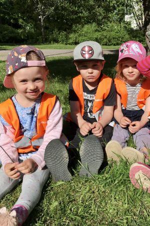 Fyra barn i dagisåldern ute i gröngräset, med reflexvästar på.