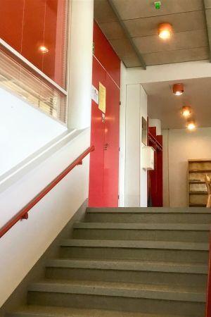 Interiör i Fokus i Karis. Vita väggar, röda trappräcken och dörrar. Grått innertak som ser smutsigt ut.