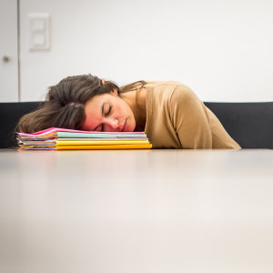 En kvinna som vilar på en hög med häften på ett konferensbord.