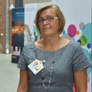 Professor Eva Österbacka i en grå klänning framför planscher och en teglad vägg.