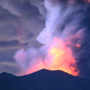 Vulkanen Agungs utbrott fotograferat från Kubu 28.11.2017. Glödande sken och rök stiger från vulkanen mot en mörk natthimmel.