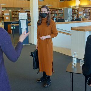 Kolme naista kirjastossa.