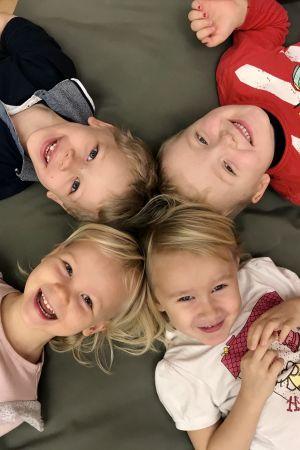 Fyra glada barn ligger på en matta.