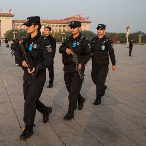 Kinesiska poliser marscherar med automatgevär i händerna och solglasögon.