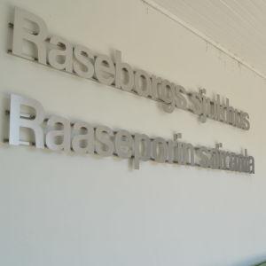 En bild på ingången till Raseborgs sjukhus i Ekenäs. På bilden syns silvriga bokstäver där det står raseborgs sjukhus.