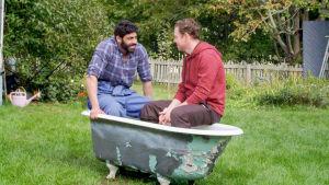 Mohamed (Bakr Hassan) och Christian (Patrick Henriksen) sitter i ett tomt badkar mitt på gräsmattan på en gård.