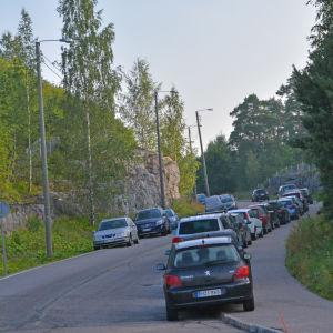 Bilar parkerade på båda sidor längs en landsväg.