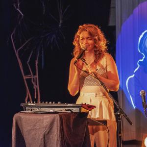 Nuori nainen laulaa mikrofoniin. Taustalla sinisävyinen taideteos, joka heijastuu taustakankaalle. Etualalla piano, jonka päällä huonekasvi.