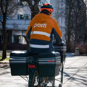 """En brevbärare på cykel. Brevbäraren har på sig en orange rock med texten """"Posti"""". Hen har ryggen vänd mot kameran."""