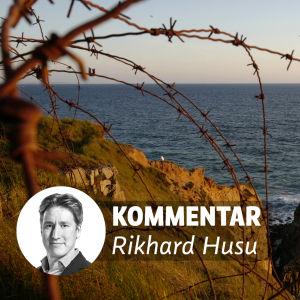 """Taggtråd ligger på klippor vid stranden. På bilden en banner med texten """"Kommentar Rikhard Husu""""."""