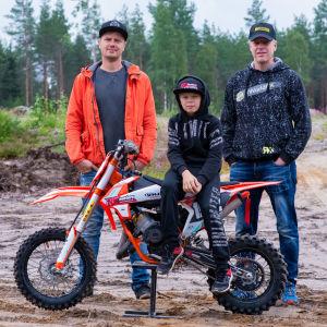 En pojke sitter på en motocrossmotorcykel, bakom honom står två män.