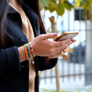 En kvinnas arm med pärlarmband, i handen håller hon en mobiltelefon.