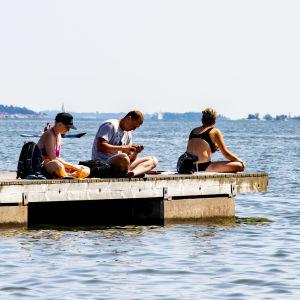 Tre personer sitter på en solig badbrygga.